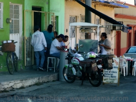The postal delivery man and others eating breakfast street side