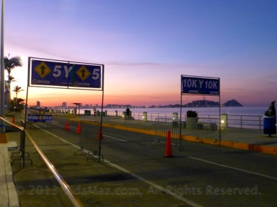 On the malecón, at dawn, signs directing 5k runners to turn around